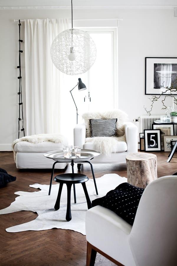 luxus wohnzimmer weiß mit luegesofa und polstersessel weiß-parkettboden mit kuhfellteppich weiß und moderne kugel pendelleuchte