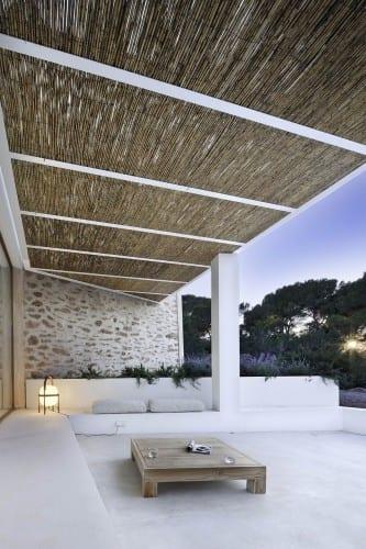 minimalisrtische terrasse gestaltung in weiß mit steinmauer und hochbettfplanzen