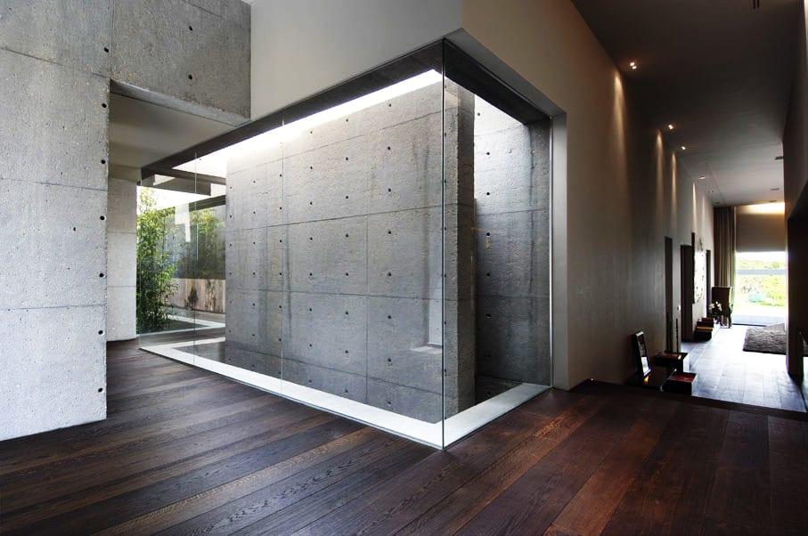minimalistisches haus mit dunklem holzboden und wänden aus sichtbetonplatten-gartengestaltung im haus