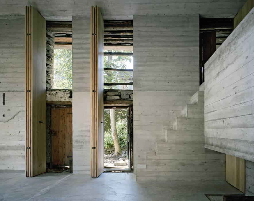 modernes wohnzimmer aus beton und innentreppe zum schlafnische