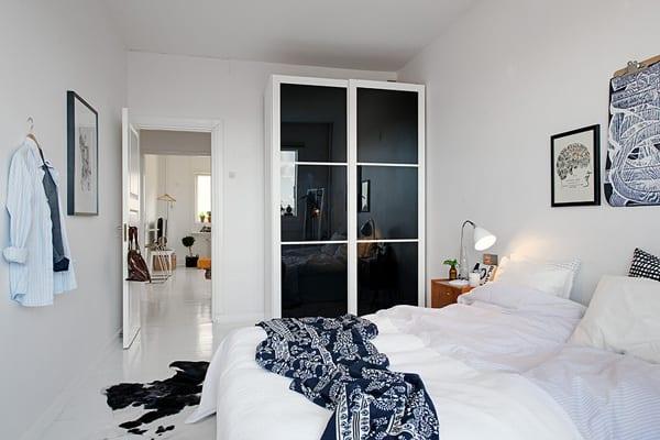 kleines schlafzimmer weiß mit kleinem Kleiderschrank weiß mit Schiebetüren aus schwarzem Glas