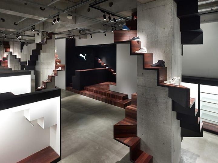 kreatives interior mit betonstützen und holztreppe als stönde für schuhen