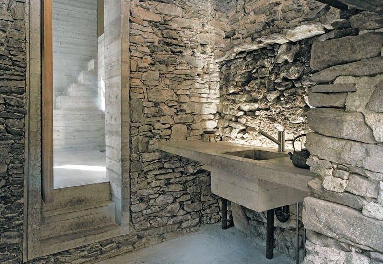 wände aus natursteinen-innentür holz mit türzarge aus beton-waschbecken aus beton mit indirekter beleuchtung