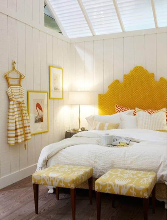 schlafzimmer dachschräge mit weißen fensterrollos- kopfbrett gelb und gelbe bilderrahmen als farbakzent
