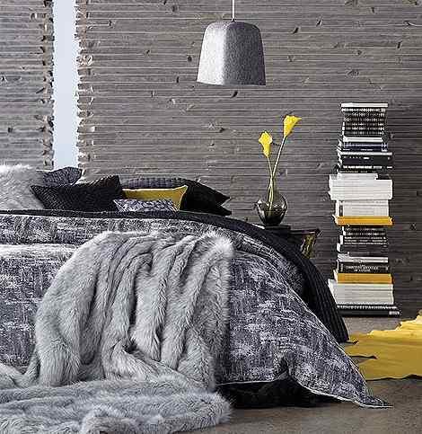 luxus schlafzimmer mit natursteinwand grau und bettwäsche in grau und sxhwarz-teppich gelb und bettdecke grau