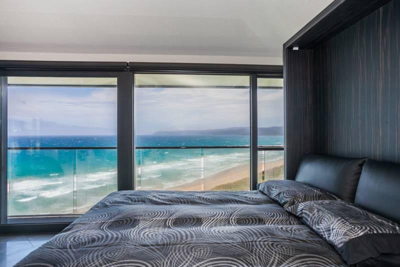 kleines schlafzimmer mit luxus bettwäsche schwarz und kopfbrett aus holz