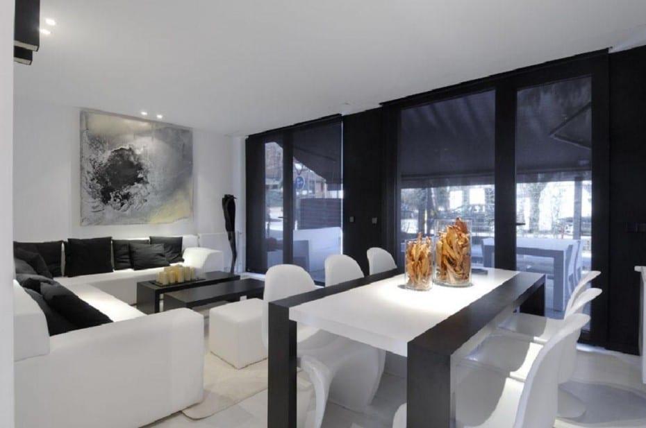 innenraumgestaltung kleines wohnzimmers mit weißem ecksofa und schwarz weißem esstisch mit weißen stühlen