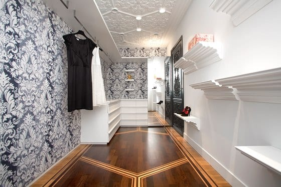 luxus ankleideraum mit holzboden und deckengestaltung mit barockmotiven-schwarze tapete mit weiße barokmotiven-kreative wandregalen