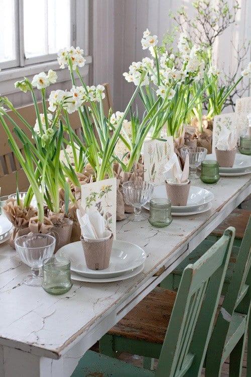 rustikale ostern tischdeko mit holztisch und holzstühlen in hellgrün