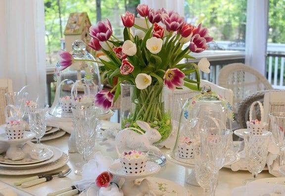 tisch eindecken mit tulpen und weißen osterkörbchen mit ostereiern