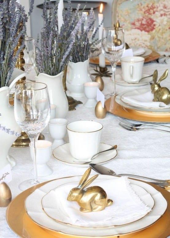 tisch eindecken mit weißer tischdecke und goldenen ostereiern