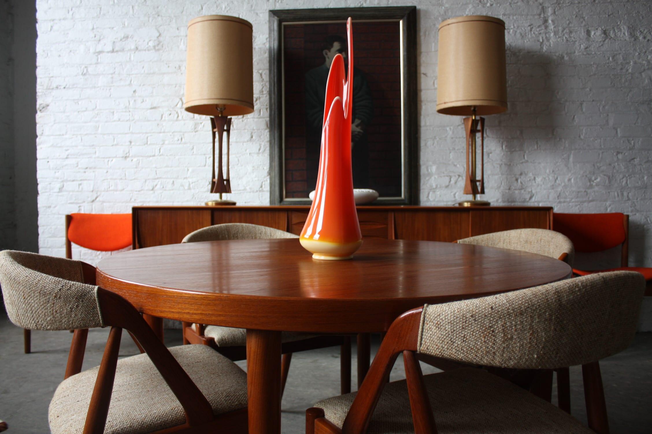 runder tisch aus holz mit esszimmerstühlen aus holz fürs esszimmer mit weißer ziegelwand und sideboard antik mit spiegel und tischlampen dekorieren