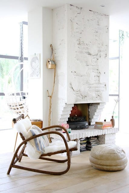 mein wohnzimmer mit kamin aus weißen ziegeln und holzsessel rustikal