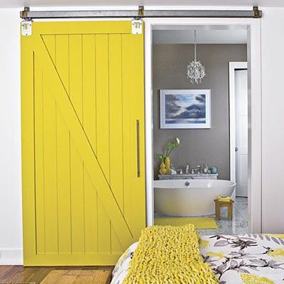 schlafzimmer mit holzschibetür gelb zim badezimmer-wandfarbe grau - bettdecke gelb