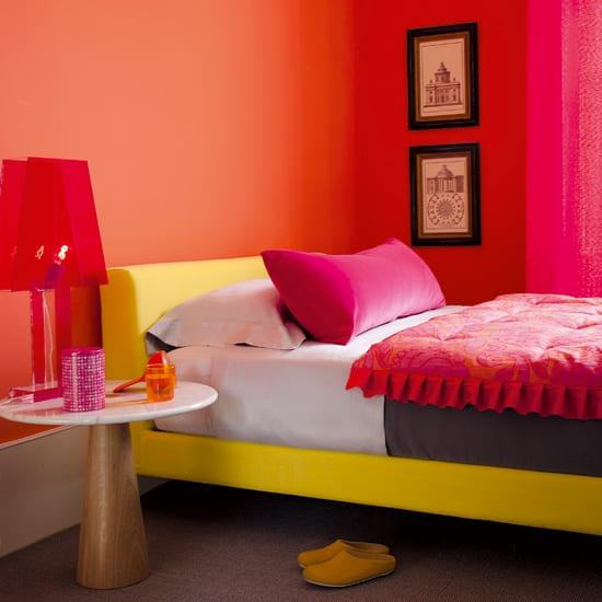 wandfarbe apricot mit gelbem bett und Akzenten in pink