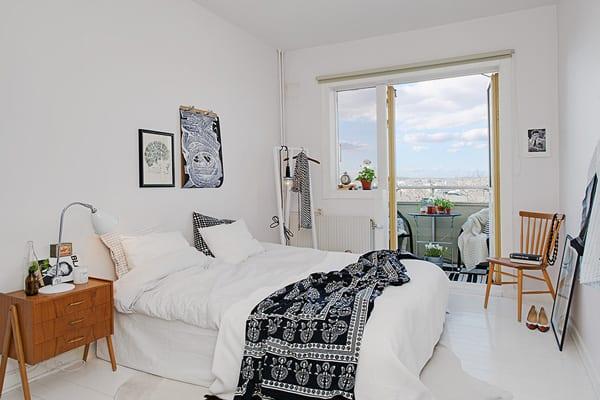 kleines appartement mit stylischem wohnzimmer design_bettdecke schwarz weiß und holzstühl