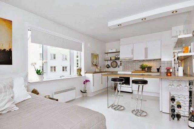 1 zimmer appartement mit kleine kücke weiß und bartheke aus holz mit barhockern schwarz