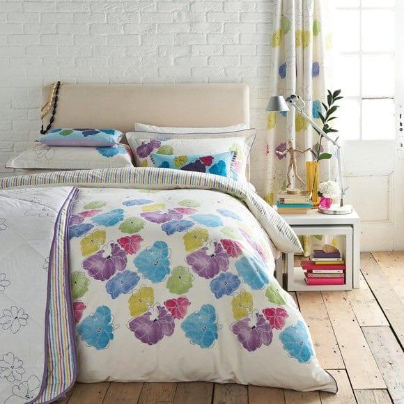 schlafzimmer gestaltung mit ziegelwand weiß und moderner bettwäsche weiß mit blumen