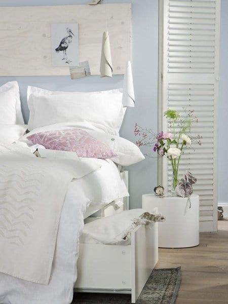 idee für elegante schlafzimmereinrichtung in weiß mit rundem nachttisch weiß und modernen pendelleuchten
