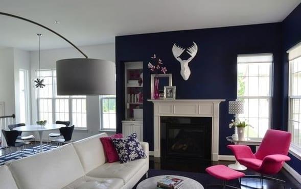 wohnzimmer farbgestaltung in weiß und blau-blaue wand mit weißem kamin und ledersofa weiß-polstermöbelstück sessel pink-weißer esstisch rund mit blauen hilzstühlen und teppich in blau weiß