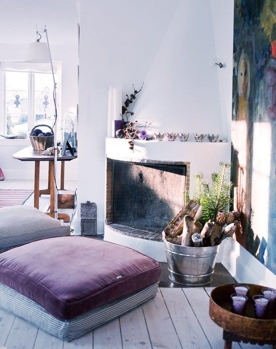 mein wohnzimmer mit rustikalem kamiöfen und lila bodenkissen