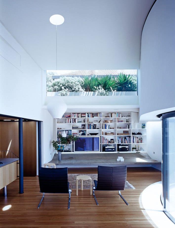 luxus wohnzimmer mit wohnwand aus weißen wandregalen- fensterband zum garten