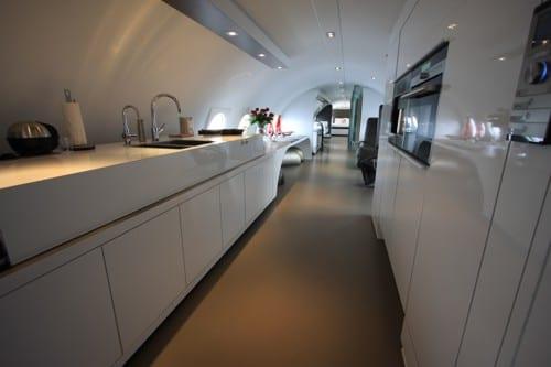 luxus flugzeug suite mit eleganter küche in weiß und eingebauten elektrogeräte