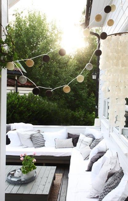 balkon terrasse mit DIY couchtisch aus paletten und sofa mit weißen kissen