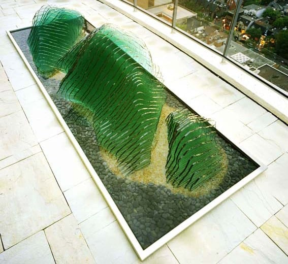 gartenskulpturen aus flachglas im teichbecken mit schwarzem kiesel