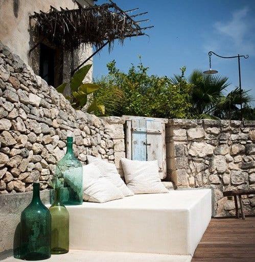 holzterrasse mit steinmauerwerk und sofa weiß