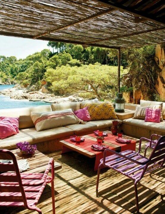 holzterrasse mit bambus überdachung und metalstühle in lila und pink