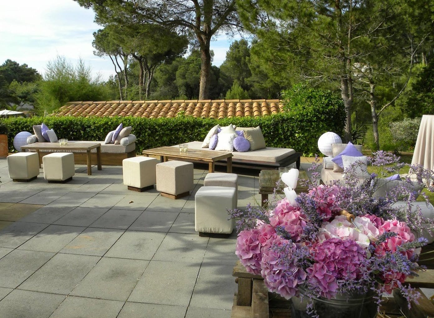 terrasse gestalten mit liegesofas aus holz  und weißen hockern