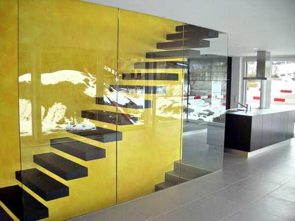 open space wohnzimmer mit gelber wand- moderne treppe schwarz mit glaswand