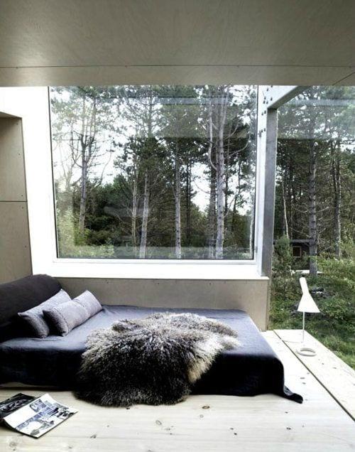 romantisches schlafzimmer panoramafenstern und holzbodenbelag_bett mit schwarzer bettwäsche dekorieren