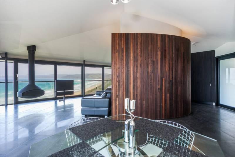 modernes wohnzimmer mit natursteinbodenbelag und hängende kamin schwarz-holzwandverkleidung von rundwand