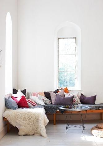 mein wohnzimmer mit bogenfenstern und holzsitzecke mit Plez und bunten kissen