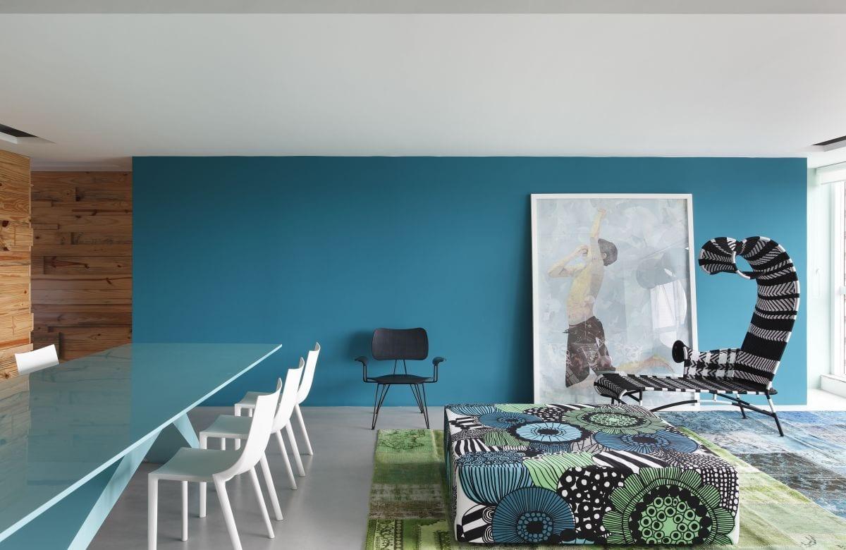 minimalistisches wohnzimmer interior mit wand blau und moderner tisch in Hellblau und weißen stühlen.traumteppich grün und blau