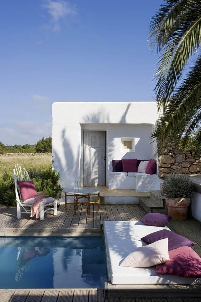 modernes haus mit ausgemauerter sitzecke weiß und pool mit sitzmatte weiß und lila kissen