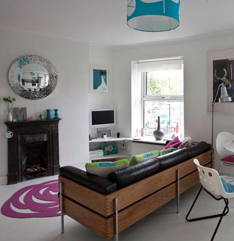 kleines wohnzimmer modern einrichten mit ledersofa schwarz-boden weiß mit traumteppich lila vor schwarzem kamin-pendelleuchte blau
