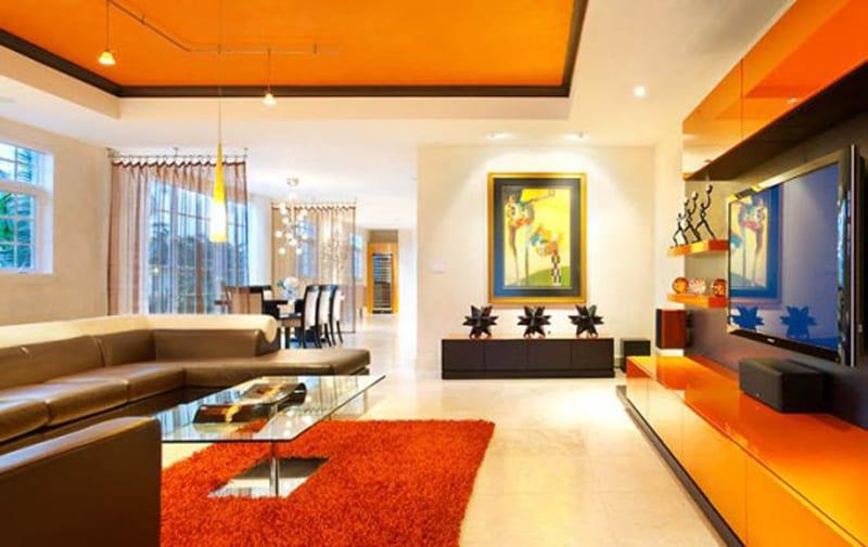 modernes wohnzimmer gestaltung mit wohnwand orange und ledersofa braun mit teppich orange-decke streichen orange