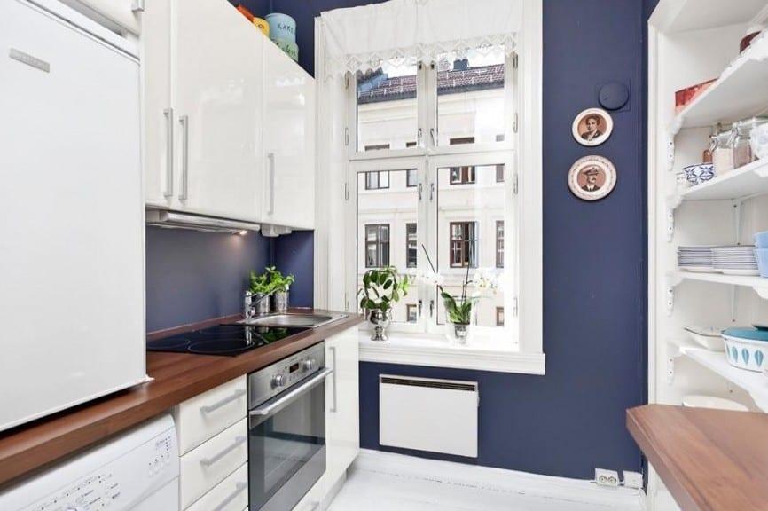 kleines appartement mit weißer küche und wandfarbe blau-küchenschränke weiß und küchenarbeitsplatte aus holz