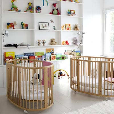 weißes babyzimmer einrichten mit wandregalen und rollenbabybetten