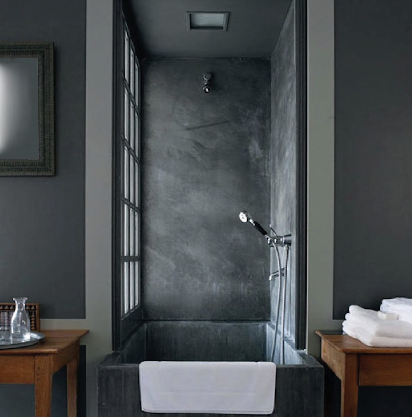 kleines badezimmer mit badewanne aus beton in nische mit fenster