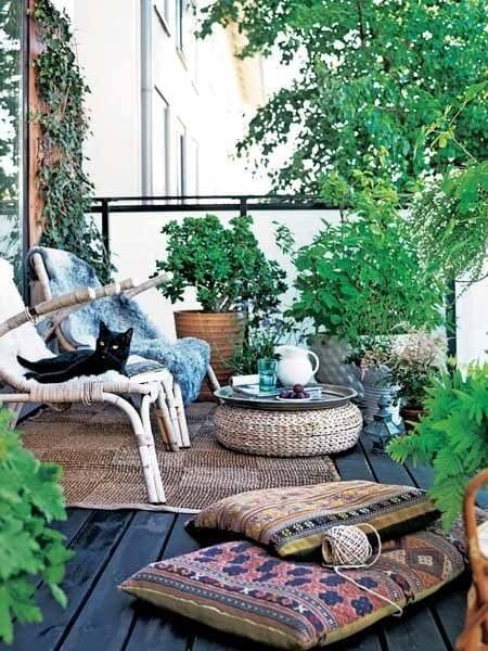 balkon mit holzboden schwarz und bambusstühlen mit rattanhocker rund