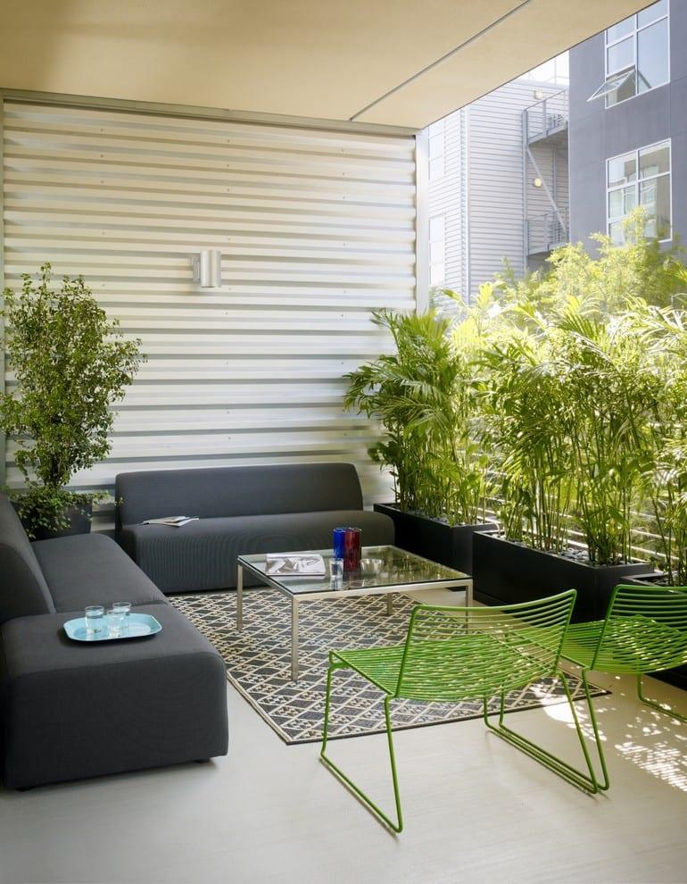balkon modern mit teppich und schwarzen planzenkisten mit bambus