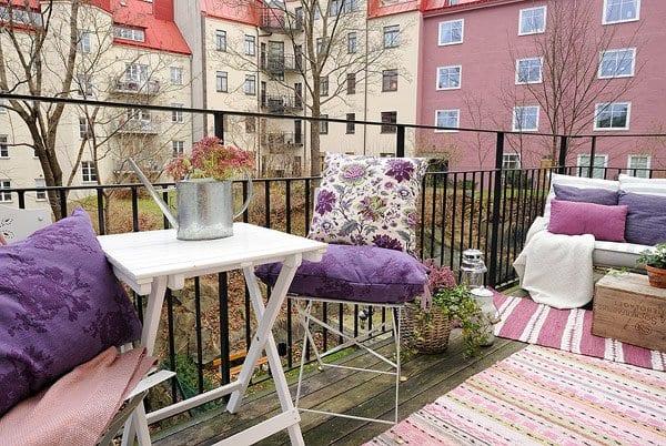 balkon ideen mit rosafarbigen teppichen und lila kissen