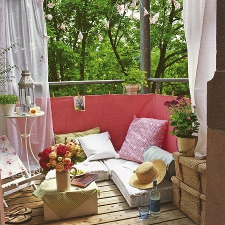 balkon terrasse mit holzboden und sitzecke aus kissen
