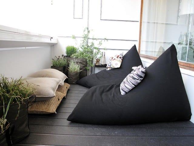 balkon mit wpc terrassendiele schwarz und kreativen blumentöpfen aus taschen