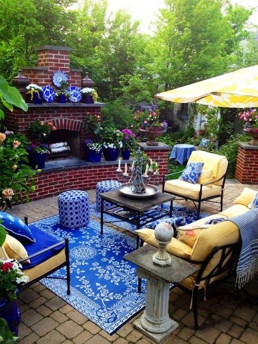 terrasse garten mit ofenkamin aus roten ziegeln mit blauen blumentöpfen dekoriert und gartenmöbel aus metall mit gelben polsterkissen und couchtisch holz