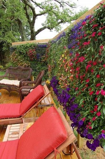 holzterrasse gestalten mit Holzliegen und Blumengarten vertikal